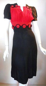 early 1940s dress with button detail.Get rid of the brown and lose the waist buttons and it wouldn't be so bad.