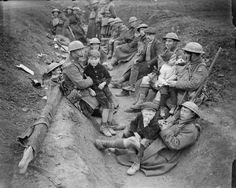 Men of the Gordon Highlanders with French refugee children in their improvised trench near Locon, 10 April 1918. They will be sent back to their village after nightfall.