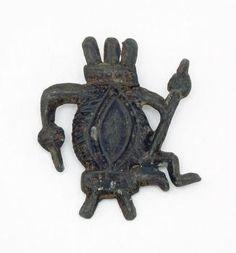 Vulva met kroon van fallussen. ca. 1350-1400.  Dit insigne wordt mogelijk gedragen als amulet voor vruchtbaarheid en voorspoed. Beschrijvingen van de fantasierijke voorstellingen zijn terug te vinden in hekserij-handboeken. Heksen zouden doen aan impotentietoverij. Hier zit een vulva  op een krukje met een spinrok in de hand.