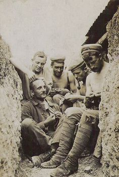 WW1: German soldiers in a trench during summer. The dugouts always faced the rear wall of the trench. Note the puttees worn by the soldier in the front; the tall leather boot has been replaced already by puttees because leather deteriorated fast in waterlogged conditions. Note also the man on the left who has taken to delousing his buddy, one little bugger at a time.