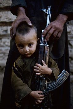 photojournalism, from the child hold the gun tide, shows how mush the child want his father to stay with him and not go to the army(killing).