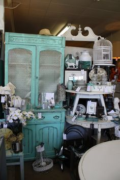flea market booth, note the one bold color on the hutch....then the table painted white and stacked and used as shelves....