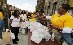 """Members of the Adventist Community Services Disaster Response team hand out bags of food to West Baltimore residents affected by the recent rioting in Baltimore, Maryland  Read more about these """"social activists"""" at http://www.columbiaunionvisitor.com/read-the-april-2015-visitor-online/"""