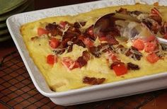 HOT BROWN CASSEROLE - Louisville's Brown Hotel has turned their traditional Hot Brown into a casserole.   For the roux: 1 C butter 3/4 C flour 2 eggs, beaten 6 C milk 1 C grated Parmesan cheese, divided 1/4 C heavy whipping cream Salt and pepper, to taste ----------------------------------- 16 slices white bread, toasted 16 slices roast turkey Paprika 1 C bacon bits  1 C tomato, seeded and diced 1/4 C chopped parsley