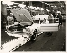 "View of men working on 1964 1/2 Mustang at Ford Motor Company plant assembly line. Handwritten on back: ""1964 1/2 Mustang, Ford Mustang."""