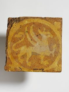 Griffin Tile | Place of origin: Dorset, England (made) Date: 1250-1300 (made) Artist/Maker: unknown (production) Materials and Techniques: Inlaid and glazed earthenware  Museum number: 1289-1892 Gallery location: Medieval and Renaissance, room 10c, case 7