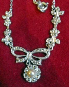 "T6730 £18 or offer + p  Silver col metal mounted (probably S/P) marquisite necklace w bow detail and w flower shaped pendant drop inset w faux pearl.  Necklace incorporates a med link chain. Measures approx 15.25"" long (inc the clasp).  There are quite a few marquisite stones missing but these are hard to spot as the detail on the necklace is rather intricate with or without these. Probably benefit from expert cleaning. Exact age unknown but probably dates from first part of last century."