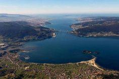 Playa de Cesantes en la Ría de Vigo, con vistas a la isla de San Simón, puente de Rande, Vigo, península del Morrazo y las islas Cíes en la desembocadura de la ría.