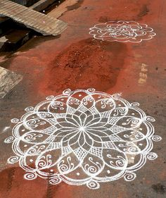 Kolam is a form of sand painting that is drawn using rice powder by female members of the family in front of their home. It is widely practiced by Hindus in South India. A kolam is a sort of painted prayer - a line drawing composed of curved loops, drawn around a grid pattern of dots. Kolams are thought to bestow prosperity to homes.