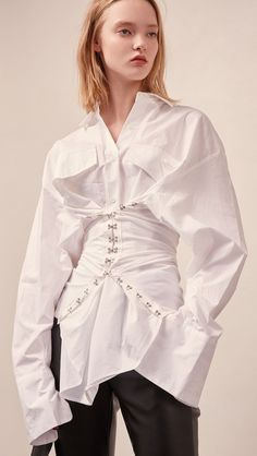 The Keira corset shirt in off-white with long sleeves, button down front, hook and eye closure for corset. Stretchy banding at back. Slim fit. COMPOSITION AND CARE Hand wash or delicate washing machin