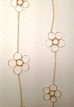"""Details This 34"""" inch long flower chain necklace features a six whimsical wire-wrapped flowers. It is available in your choice of 14-karat gold fill or sterling silver. Made of: 14-karat Gold Fill, St"""