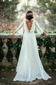 Chica con un vestido de novia con escote en la espalda parada sobre un barandal de piedra