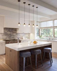 Skinny pendant lamps hang over a kitchen island made of Calacatta marble.