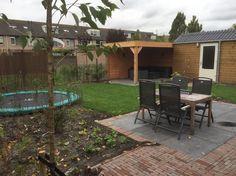Gezind tuin met terras in de zon, veranda, trampoline en gazon op te spelen of te luieren. Foto genomen vrijwel direct na de aanleg herfst 2014