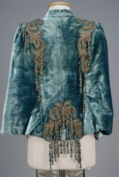 """PARIS BEADED DOLMAN CARRIAGE JACKET, 1880s. Aquamarine plush decorated with silver metallic and turquoise cord scrolls with turquoise and gold beads, knotted cord tassels with beaded loops, silk satin lining. Label """"Walles 8, Rue de Choiseuls, 8 Paris""""."""