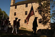 Members of the 1st Virginia Regiment, a Revolutionary War reenactment group, march in front of George Washington's Gristmill at the Mount Vernon Estate, before a 2005 ceremony to lay a cornerstone at the site of the soon-to-be reconstructed George Washington's Distillery and Museum. The cornerstone is a sandstone block from the original 1793 U.S. Capitol and from the same vein of sandstone which Washington used to build his first distillery in 1797. (CQ Roll Call File Photo) #flag