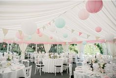 Pastel Paper Lanterns Hanging from Marquee Ceiling. See more of our floral creations at www.passionforflowers.net