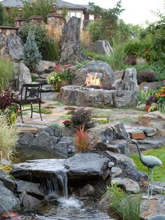 Inspiration for a mid-sized mediterranean full sun backyard formal garden in Denver with natural stone pavers and a fountain.