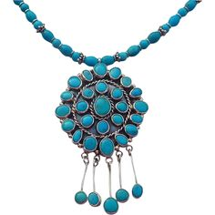 Turquoise Southwestern Necklace The focal of this lovely southwestern necklace is a very high quality, well made pendant with 25 turquoise stone with flecks of pyrite set into smooth bezels. Interspersed between the stones are rope braids. It has a mounded shape and measures 2 inches in diameter with 1 inch turquoise dangles. Kingman turquoise 6-8mm beads and sterling silver spacer beads make up the 22 inch necklace with a sterling silver hook clasp and 2 inch extender chain.