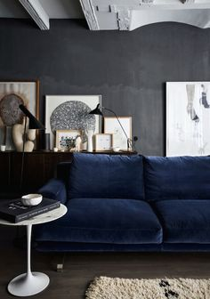 Deep blue velvet sofa, dark walls and monochromatic art in the living room.