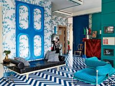 In the same space, a Blair Thurman work is mounted above a daybed accented with pillows in a Le Manach fabric; Playmobil made the large toy soldier, and the tête-à-tête is by Verner Panton.