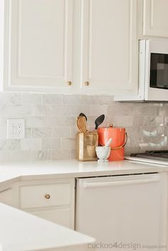 Gorgeous kitchen with creamy white cabinets accented with brass hardware paired with polished Hampton Carrara Marble subway tiled backsplash paired with is Galaxies countertop by Quartz Maste as well as Target Nate Berkus Decorative Bucket Gold Rectangle and persimmon orange ice bucket with brass trim.