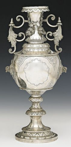 <b>A SILVER TROPHY VASE BY EDWARD FISCHER, GEELONG, CIRCA1880</b> <br /> of knopped baluster form with scrolling handles, engraved and chased with vine leaves and rams heads in shield cartouches, hallmarked Fischer, Geelong to the base, together with a glass dome and ebonised circular stand <br /> <br /> 792GMS, 32.5CM HIGH