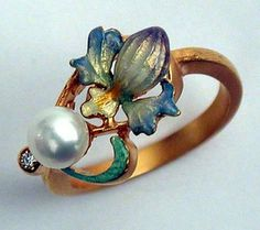I believe that looks like an iris. This is exquisite! I could probably fake something like it but what a shame to make a cheap copy. ~  Masriera Pearl Leaf Ring