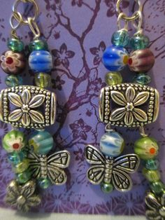 """silver flower beads ; blue/green glass seed beads silver findings ,lower and butterfly charms  2  3/4"""" long product $ E036  $10.00"""