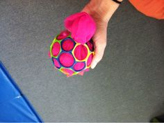 Pull a lightweight scarf out of a holey ball :) Great for pinching and strengthening as well as bilateral coordination, motor planning...tons of stuff!