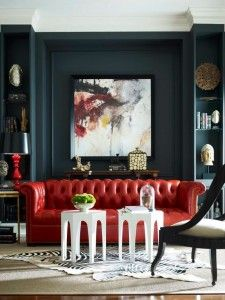Dramatic black walls and bookshelves with red leather tufted sofa