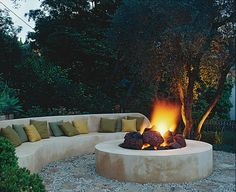 Designing with fire features: The fire sits in a 12-foot circle of flagstone and gravel, the same materials used for the path that winds up to this cozy hideaway. Rounded chunks of lava stone break up the sleek design giving the fire pit a more authentic, rustic feel. Photo by Tim Street-Porter. #gardendesign #autumn #firepit