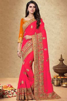 Bright Pink silk saree with orange silk blouse, embellished with dori work, resham work and sequins work. Saree with Round Neck, Quarter Sleeve. It comes with unstitch blouse, it can be stitched 32 to 58 sizes. #bright pink #silk #saree #blouse #Andaazfashion #UK