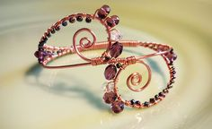 Czech glass, Toho glass and Swarovski crystal beads are wire wraped in a delicate swirled copper bonded aluminum bangle.