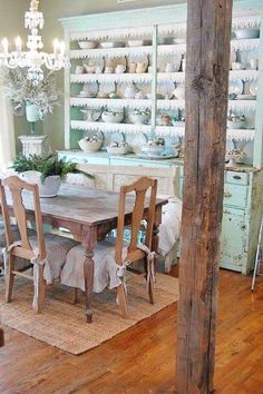 Shabby chic dining room with old wood table and aqua hutch