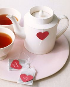 Warm someone up by adding a handwritten note to a tea bag. Cut two hearts out of red construction paper using a heart-shaped crafter's hole punch (available at crafts stores). Use a metallic pen to write a short message on one of the hearts. Next, remove a tea-bag tag and, at the end of the string, affix two hearts, back-to-back, using double-sided tape or a stapler. Package bags to give as a present, or steep one in hot water and serve.