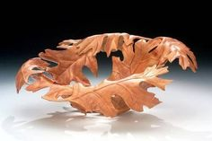 Andi Wolfe   Red Oak leaf motif carved from an African Sumac bowl by ivy