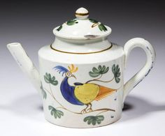 ENGLISH PEARLWARE CERAMIC MINIATURE TEAPOT, toy-sized, having a polychrome-painted bird design in blue, yellow, orange, and brown surrounded by small painted foliage, foliage painted on cover with brown line on finial, shoulder, handle, and spout. Unmarked. Staffordshire and other areas.