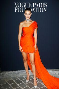 Bella Hadid in an orange Giambattista Valli dress at the Vogue foundation dinner in Paris