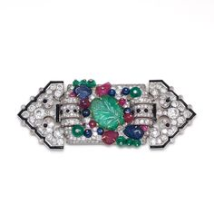 A rare 'Tutti Frutti' diamond brooch, by Cartier Of stylised floral and foliate design, the central plaque embellished with an emerald carve...