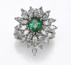 An emerald and diamond ring  centering a pear-shaped emerald, weighing approximately: 1.00 carat; estimated total diamond weight: 1.80 carats; mounted in platinum