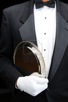 Picture of Closeup of af butler with a silver tray under his arm. Man is wearing a tuxedo and white gloves showing torso only in vertical format. Downton Abbey, Caviar, Gentleman, Wearing A Tuxedo, Butler Service, Silver Trays, Black Tie Affair, Glamour, Butler Pantry