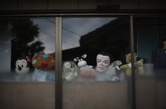 Namie, Japan: Toys and novelty masks in the window of a home inside the radiation contamination exclusion zone – five years on from the Fukushima Daiichi nuclear disaster