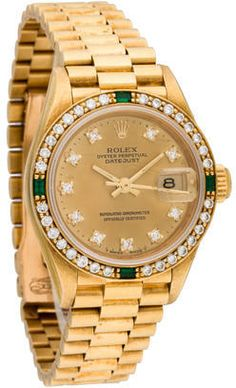 Ladies' 18K yellow gold 26mm Rolex Oyster Perpetual Datejust automatic watch with diamond and emerald bezel, champagne dial, diamond hour markers, stick hands, cyclops date display, signed crown, President link bracelet and deployant closure.