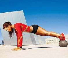 24-Minute At-Home Boot Camp! 1st Station, 1st Move: Start with Knee Tuck. Hold a plank with feet on medicine ball, hands on ground (as shown). Keeping left foot on ball, bring right knee toward chest, then kick right leg out to side. Return to start