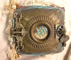 front cover is a piece of an old carriage lantern painted and adorned with other found items such as old keys, parts of an old necklace for a clasp, and an antique drawer pull. Hand distressed fibers decorate the spine. Many collage and painted tags slip in between the pages of each section to journal on. A Meaningful Life Journal - Cloth Paper Scissors