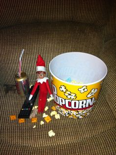 "Elf R and R  Found our elf sitting in recliner, eating popcorn, cheez-its, crackers, chips, cookies and marshmallows, drinking a diet coke with the remote in his hand watching…  ""Elf"", of course!"