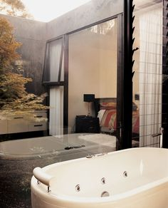 "The guest bathroom  includes glass walls that look out onto one of the house's ""voids,"" in which pear trees grow."