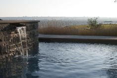 Built into a sloping site, this residence included a complex series of levels and retaining walls. The property slopes to the water with its own isthmyth and small stream bordering the property line. Pool Water Features, Retaining Walls, Pools, Building, Swimming Pools, Buildings, Construction, Ponds, Architectural Engineering