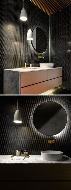 This bathroom has its walls covered in tiny black hexagonal tiles, and the vanity and mirror both feature hidden lighting.